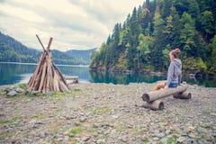 Όμορφο κορίτσι σε ένα hoodie Μπλε λίμνη βουνών πράσινη Η πυρκαγιά Στοκ Εικόνες