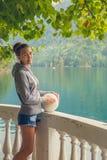 Όμορφο κορίτσι σε ένα hoodie Μπλε λίμνη βουνών πράσινη Στοκ Φωτογραφίες