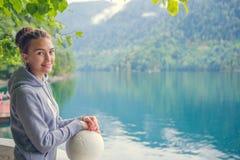 Όμορφο κορίτσι σε ένα hoodie Μπλε λίμνη βουνών πράσινη Στοκ φωτογραφία με δικαίωμα ελεύθερης χρήσης