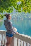 Όμορφο κορίτσι σε ένα hoodie Μπλε λίμνη βουνών πράσινη Στοκ Εικόνες