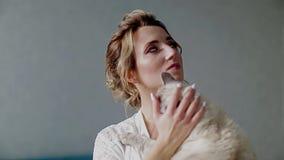 Όμορφο κορίτσι σε μια άσπρη ρόμπα που κρατά μια σιαμέζα γάτα και που κτυπά το χέρι του Κτυπά το λαιμό του φιλμ μικρού μήκους