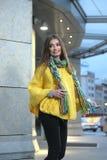 Όμορφο κορίτσι σε μια κίτρινη πλεκτή poncho μόνιμη θέση Στοκ Φωτογραφίες