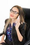 Όμορφο κορίτσι σε μια συνεδρίαση επιχειρησιακών κοστουμιών σε μια πολυθρόνα δέρματος Στοκ Φωτογραφίες