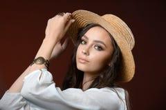 Όμορφο κορίτσι σε μια τοποθέτηση καπέλων αχύρου στο στούντιο σε ένα καφετί υπόβαθρο στοκ εικόνα