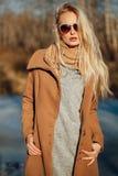 Όμορφο κορίτσι σε μια τοποθέτηση παλτών στα πλαίσια μιας φύσης άνοιξη Στοκ φωτογραφία με δικαίωμα ελεύθερης χρήσης