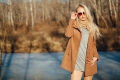 Όμορφο κορίτσι σε μια τοποθέτηση παλτών στα πλαίσια μιας φύσης άνοιξη Στοκ Φωτογραφίες