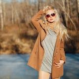 Όμορφο κορίτσι σε μια τοποθέτηση παλτών στα πλαίσια μιας φύσης άνοιξη Στοκ Εικόνες