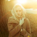 Όμορφο κορίτσι σε μια τοποθέτηση παλτών στα πλαίσια μιας φύσης άνοιξη Στοκ εικόνα με δικαίωμα ελεύθερης χρήσης