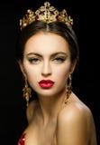 Όμορφο κορίτσι σε μια χρυσή κορώνα και σκουλαρίκια σε ένα σκοτεινό backgrou Στοκ Εικόνα
