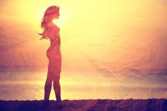 Όμορφο κορίτσι σκιαγραφιών στο ηλιοβασίλεμα Στοκ Εικόνες