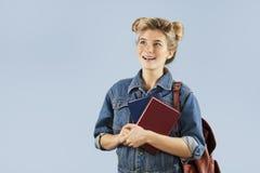 Όμορφο κορίτσι σπουδαστών σε ένα σακάκι τζιν με ένα σακίδιο πλάτης στους ώμους της στο στούντιο σε ένα μπλε υπόβαθρο Η έννοια στοκ φωτογραφία