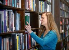 Όμορφο κορίτσι σπουδαστών σε μια βιβλιοθήκη Στοκ φωτογραφίες με δικαίωμα ελεύθερης χρήσης