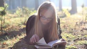 Όμορφο κορίτσι στα γυαλιά που διαβάζει ένα βιβλίο στο δάσος φιλμ μικρού μήκους