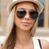 Όμορφο κορίτσι στα γυαλιά ηλίου και καπέλο που στέκεται στον τοίχο Στοκ εικόνες με δικαίωμα ελεύθερης χρήσης