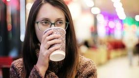 Όμορφο κορίτσι στα γυαλιά που πίνει τον καφέ στον καφέ απόθεμα βίντεο