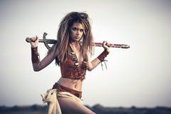 Όμορφο κορίτσι στα ενδύματα ενός Βίκινγκ ή του Αμαζονίου, με ένα swor στοκ εικόνα