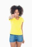 Όμορφο κορίτσι στα κίτρινα καυτά εσώρουχα μπλουζών και τζιν που δείχνει στη κάμερα Στοκ Εικόνες