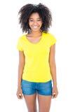 Όμορφο κορίτσι στα κίτρινα καυτά εσώρουχα μπλουζών και τζιν που χαμογελά στη κάμερα Στοκ Φωτογραφίες