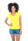 Όμορφο κορίτσι στα κίτρινα καυτά εσώρουχα μπλουζών και τζιν που χαμογελά στη κάμερα Στοκ φωτογραφία με δικαίωμα ελεύθερης χρήσης