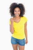 Όμορφο κορίτσι στα κίτρινα καυτά εσώρουχα μπλουζών και τζιν ενθαρρυντικά στη κάμερα Στοκ Εικόνα