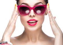 Όμορφο κορίτσι στα κόκκινα γυαλιά ηλίου με το φωτεινό makeup και τα ζωηρόχρωμα καρφιά Πρόσωπο ομορφιάς στοκ φωτογραφία με δικαίωμα ελεύθερης χρήσης