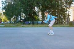 Όμορφο κορίτσι στα μπλε σαλάχια κυλίνδρων στην παιδική χαρά Στοκ Εικόνα