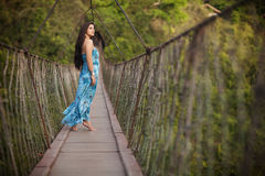 Όμορφο κορίτσι στην ανασταλμένη ξύλινη γέφυρα Στοκ Εικόνα