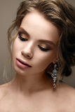 Όμορφο κορίτσι στην εικόνα μιας νύφης με τα φωτεινά σκουλαρίκια Πρότυπο με ένα ευγενές makeup στους μπεζ τόνους Στοκ φωτογραφίες με δικαίωμα ελεύθερης χρήσης