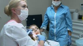 Όμορφο κορίτσι στην εξέταση από τον οδοντίατρο γιατρών απόθεμα βίντεο