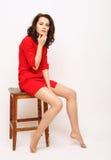 Όμορφο κορίτσι στην κόκκινη συνεδρίαση φορεμάτων σε ένα σκαμνί Στοκ φωτογραφίες με δικαίωμα ελεύθερης χρήσης
