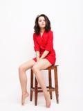 Όμορφο κορίτσι στην κόκκινη συνεδρίαση φορεμάτων σε ένα σκαμνί Στοκ φωτογραφία με δικαίωμα ελεύθερης χρήσης