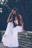 Όμορφο κορίτσι στην πολύ άσπρη συνεδρίαση φορεμάτων, αφηρημάδα στο πάρκο Στοκ εικόνα με δικαίωμα ελεύθερης χρήσης
