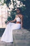 Όμορφο κορίτσι στην πολύ άσπρη συνεδρίαση φορεμάτων, που θέτει στο πάρκο Στοκ φωτογραφία με δικαίωμα ελεύθερης χρήσης