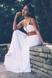 Όμορφο κορίτσι στην πολύ άσπρη συνεδρίαση φορεμάτων, που θέτει στο πάρκο Στοκ Εικόνες