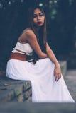 Όμορφο κορίτσι στην πολύ άσπρη συνεδρίαση φορεμάτων, που θέτει στο πάρκο Στοκ φωτογραφίες με δικαίωμα ελεύθερης χρήσης