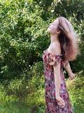 Όμορφο κορίτσι στη floral στάση φορεμάτων στον κήπο. Στοκ εικόνες με δικαίωμα ελεύθερης χρήσης