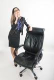 Όμορφο κορίτσι στις στάσεις επιχειρησιακών κοστουμιών δίπλα σε μια καρέκλα δέρματος Στοκ Εικόνες