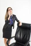 Όμορφο κορίτσι στις στάσεις επιχειρησιακών κοστουμιών δίπλα σε μια καρέκλα δέρματος Στοκ φωτογραφίες με δικαίωμα ελεύθερης χρήσης