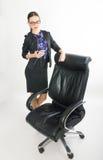 Όμορφο κορίτσι στις στάσεις επιχειρησιακών κοστουμιών δίπλα σε μια καρέκλα δέρματος Στοκ εικόνες με δικαίωμα ελεύθερης χρήσης