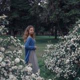Όμορφο κορίτσι στον κήπο ανθών Στοκ Εικόνες