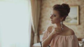 Όμορφο κορίτσι στον καθρέφτη που βάζει σε ένα σκουλαρίκι απόθεμα βίντεο