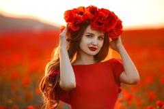 Όμορφο κορίτσι στον κόκκινο τομέα παπαρουνών στο ηλιοβασίλεμα Το ελεύθερο ευτυχές En γυναικών Στοκ Φωτογραφίες