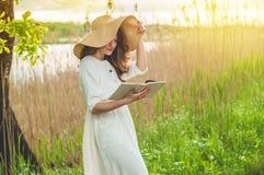 Όμορφο κορίτσι στον τομέα που διαβάζει ένα βιβλίο Η συνεδρίαση κοριτσιών σε μια χλόη, ανάγνωση ένα βιβλίο Υπόλοιπο και ανάγνωση στοκ φωτογραφία με δικαίωμα ελεύθερης χρήσης