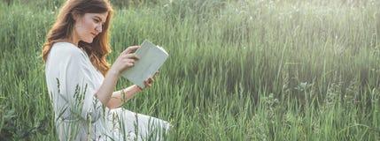 Όμορφο κορίτσι στον τομέα που διαβάζει ένα βιβλίο Η συνεδρίαση κοριτσιών σε μια χλόη, ανάγνωση ένα βιβλίο Υπόλοιπο και ανάγνωση στοκ εικόνες με δικαίωμα ελεύθερης χρήσης