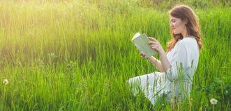Όμορφο κορίτσι στον τομέα που διαβάζει ένα βιβλίο Η συνεδρίαση κοριτσιών σε μια χλόη, ανάγνωση ένα βιβλίο Υπόλοιπο και ανάγνωση στοκ εικόνες
