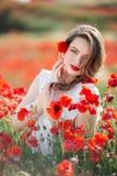 Όμορφο κορίτσι στον τομέα των λουλουδιών παπαρουνών, χρόνος άνοιξη Στοκ Φωτογραφίες
