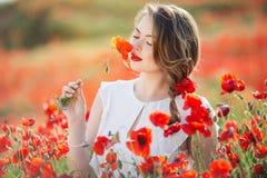 Όμορφο κορίτσι στον τομέα των λουλουδιών παπαρουνών, χρόνος άνοιξη Στοκ Εικόνες
