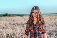 Όμορφο κορίτσι στον τομέα brunette, με τη μακριά τρίχα brunette, που χαλαρώνει στη φύση, κινηματογράφηση σε πρώτο πλάνο Στοκ Φωτογραφία