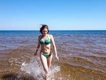 Όμορφο κορίτσι στους παφλασμούς του λάμποντας νερού της μπλε θάλασσας Στοκ Φωτογραφία