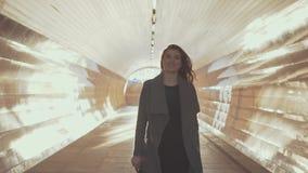 Όμορφο κορίτσι στους περιπάτους γυαλιών ηλίου μέσω της ηλιόλουστης σήραγγας στο παλτό στο ηλιοβασίλεμα απόθεμα βίντεο
